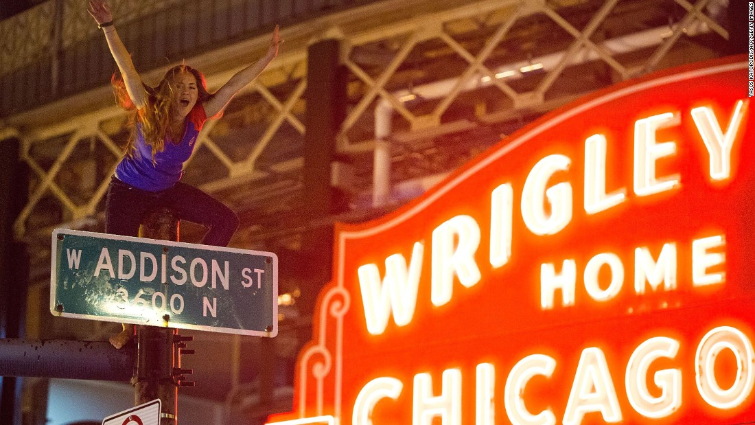 A Chicago fan straddles a street pole outside Wrigley Field as people gather to celebrate the Cubs' dramatic win.