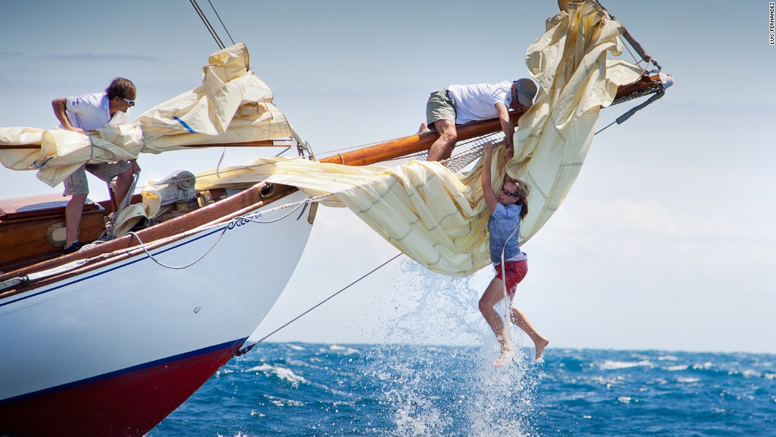 The bow woman of the yacht Gipsy loses her balance following a wave but is able to climb back on board thanks to a crew member during the Puig Vela Classica Barcelona. Luis Fernandez captured the action.