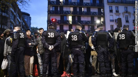 A line of police restrain migrants during Friday morning's evacuation of the camp in Paris.