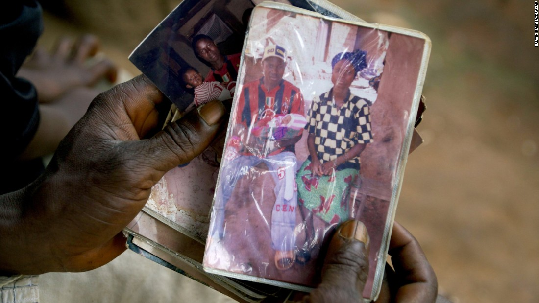 "Emile Ouamouno, a 2-year-old boy in the southern Guinea village of Meliandou, was identified as ""patient zero"" in the Ebola outbreak circa 2014. Emile died of the disease, as did several of his family members. Emile's father, Etienne Ouamouno, holds a picture of his second wife, Sia Dembadouno, and Emile."