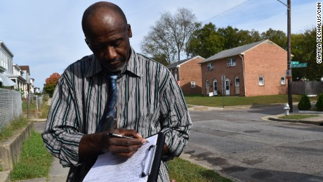 Muhammad As-saddique Abdul-Rahman writes down a resident's email address in the Blackwell neighborhood of Richmond, Virginia, on October 30, 2016.