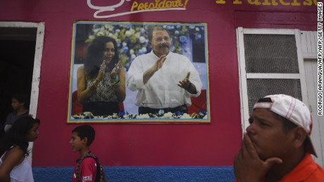 People stand next to propaganda of Nicaraguan President Daniel Ortega and her wife Rosario Murillo in Masaya, 30 km southeast of Managua, on November 3, 2016, ahead of the general elections to take place next November 6.  Surveys indicate that Nicaragua's first couple are more than likely to emerge the winners of elections that will hand Ortega a fourth mandate, and Murillo her first as his vice president. / AFP / RODRIGO ARANGUA        (Photo credit should read RODRIGO ARANGUA/AFP/Getty Images)