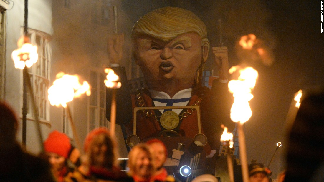 Thousands of people line the narrow streets of Lewes to watch the bonfire societies parade past with their effigies in a torch-lit procession. Here another incarnation of Trump is seen.