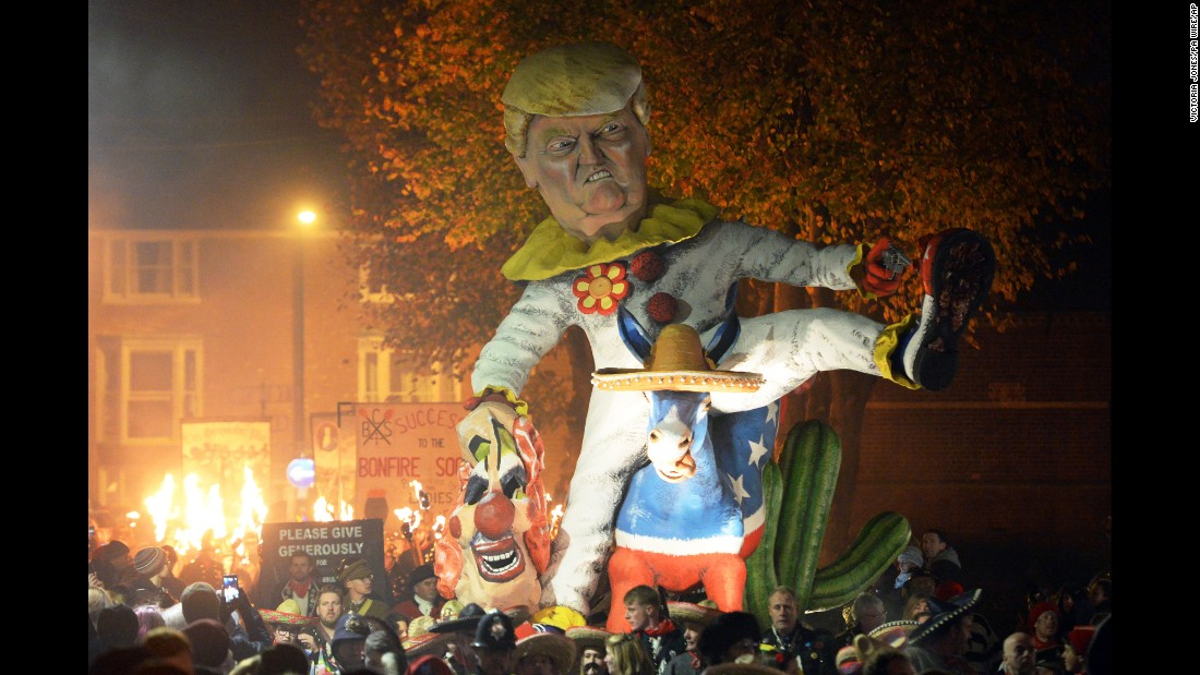 An effigy of Trump dressed as a clown riding a donkey is paraded down the street on November 5 in Lewes. After the procession, the crowds -- and their giant effigies -- disperse toward several separate bonfire parties, where the figures are blown apart by fireworks.