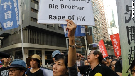 A protester raises a placard as thousands of people march through a downtown street in Hong Kong, Sunday.