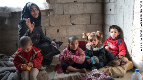 Rana is raising four children, aged 4 to 6, in a small two-bedroom apartment in an unfinished building in Damascus.