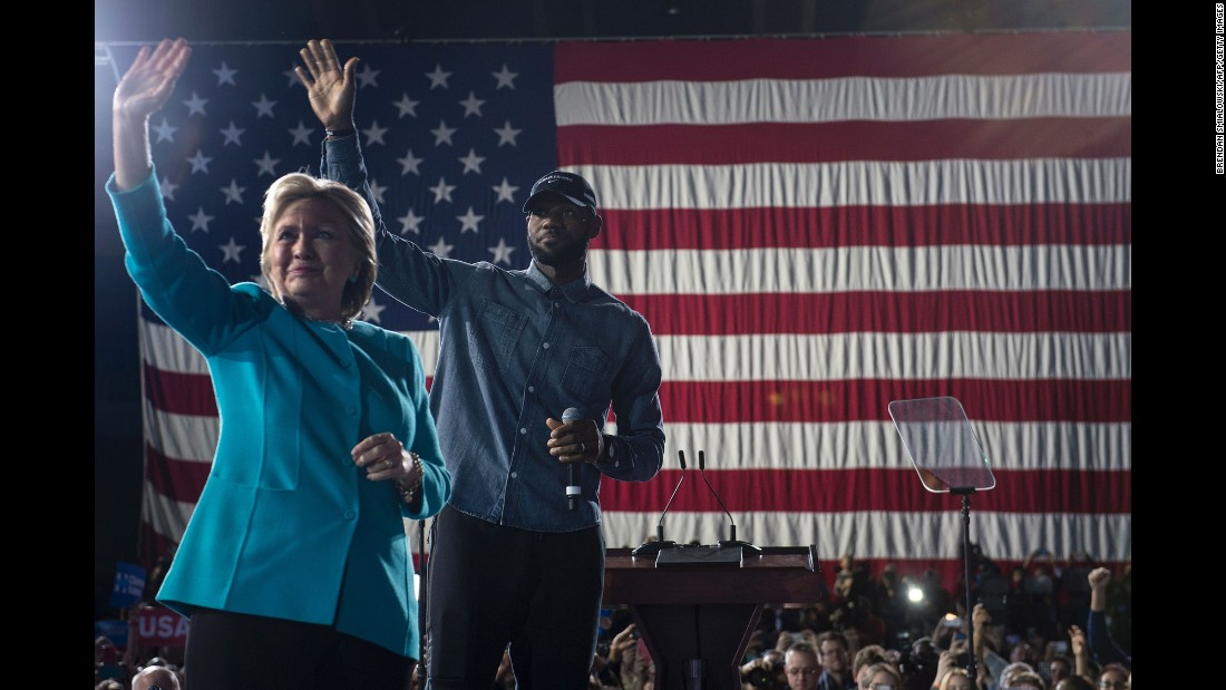 Clinton and NBA basketball player LeBron James wave to a crowd in Cleveland on November 6.