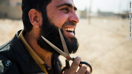 An Iraqi man who fled the fighting in Mosul uses a pair of scissors to trim his beard.