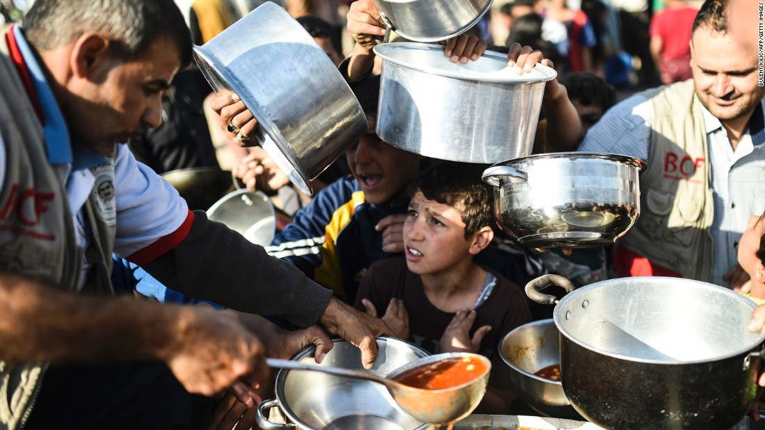 People line up to receive food at a refugee camp in the Khazir region on November 5. Thousands are taking refuge in camps set up for internally displaced people.