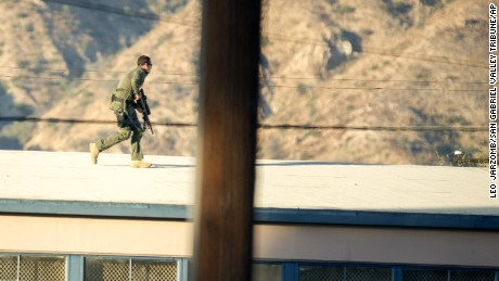 A SWAT team sniper moves atop a building to cover a suspect on Fourth Street in Azusa, California.