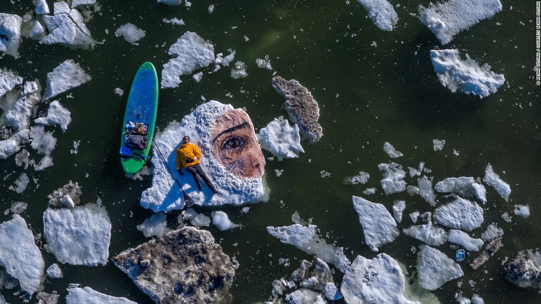 "This striking piece of art, titled ""What if I Fly"", is Yoro's latest project. Painted on the disappearing ice floes near Baffin Island, Canada, it features the portrait of a local Inuit girl. The goal of Yoro's work? ""To ignite a sense of urgency towards climate change in those who stumble upon these murals,"" he tells CNN. (Photo credit: <a href=""https://www.instagram.com/renan_ozturk/?hl=en"" target=""_blank"">Renan Ozturk</a>)"