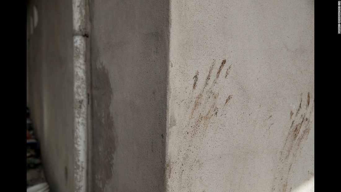 Handprints are seen on a wall.
