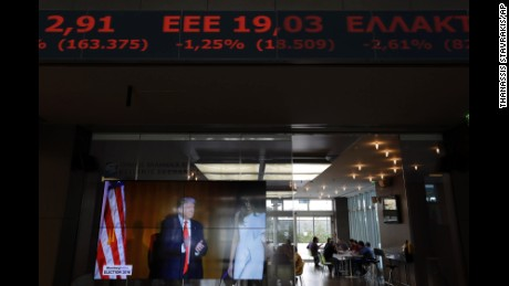 A TV screen shows U.S. President-elect Donald Trump under a ticker screen showing falling stocks in red at the Athens' Stock Exchange on Wednesday, Nov. 9, 2016. European stock markets and Wall Street futures have trimmed a chunk of their early losses after a relatively soft victory speech from Trump. (AP Photo/Thanassis Stavrakis)