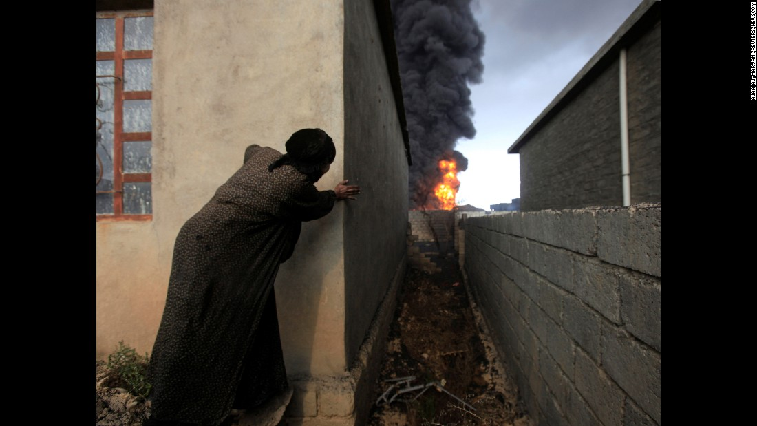 "A woman watches oil wells set ablaze by ISIS militants in Qayyara, Iraq, on Friday, November 4. <a href=""http://www.cnn.com/2016/11/05/middleeast/iraq-mosul-offensive/index.html"" target=""_blank"">As the fight to retake Mosul from ISIS</a> rages on, ISIS militants have been <a href=""http://edition.cnn.com/2016/10/12/world/burning-oil-wells-isis-iraq/"" target=""_blank"">setting oil wells on fire</a> in the hopes of obscuring the views of Iraqi and coalition warplanes."
