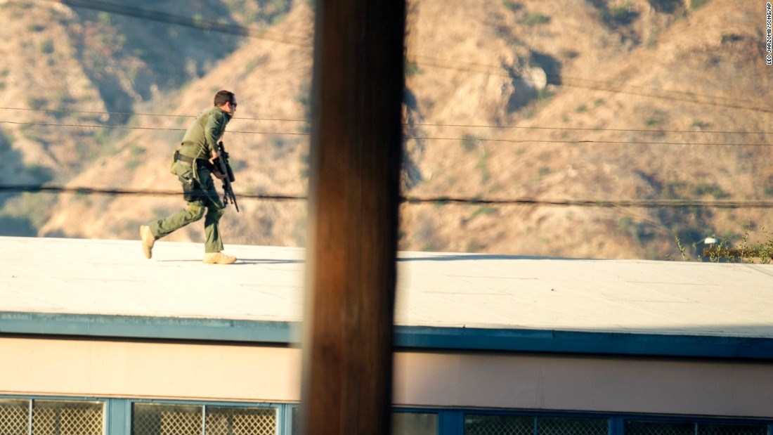 "A SWAT team sniper moves atop a building to cover a barricaded suspect in Azusa, California, on Tuesday, November 8. One person was killed and two were injured after a man opened fire near a Southern California polling station. The suspected shooter had been ""bingeing on cocaine,"" <a href=""http://www.cnn.com/2016/11/08/politics/la-area-polling-station-on-lockdown-after-shots-nearby-at-least-two-victims/"" target=""_blank"">police said</a>."