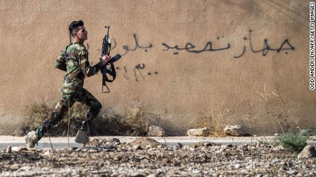 A Peshmerga fighter runs to take position in the town of Bashiqa, near Mosul.
