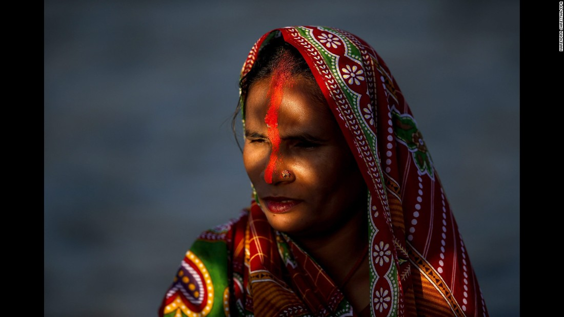 A Nepalese woman prays to the setting sun while standing in the Bagmati River during the Chhath Puja festival in Kathmandu, Nepal, on Sunday, November 6. Chhath Puja is celebrated in honor of the Hindu sun God Surya, and sees people come together to worship for a peaceful and prosperous life and good will.