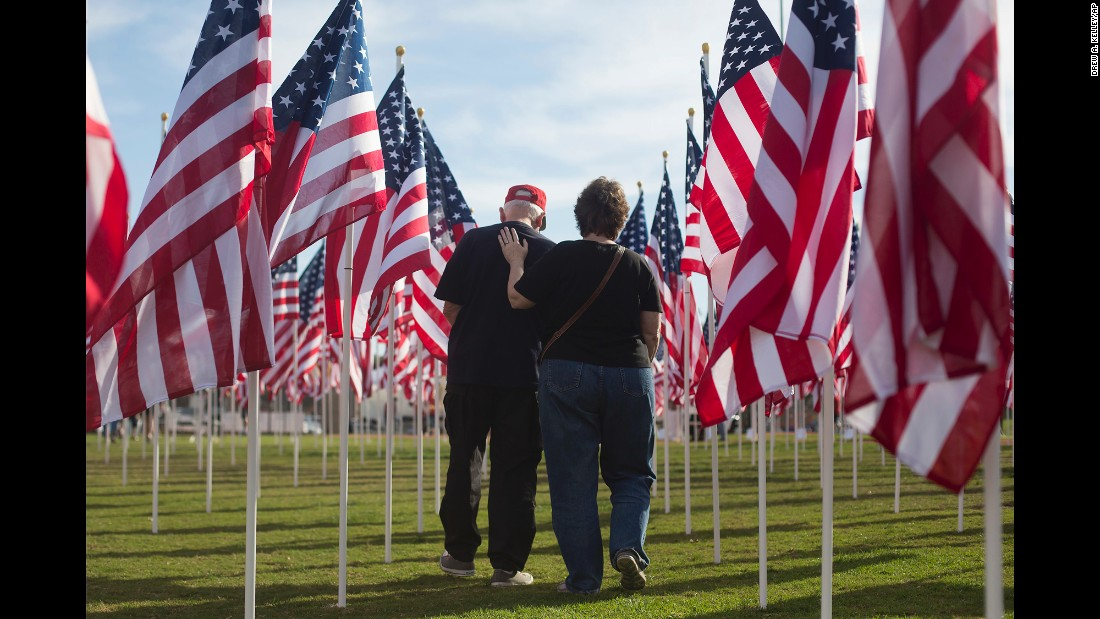 Tambra Hofstetter, right, comforts her husband, Bruce Hofstetter, after visiting a flag honoring his high school friend Leo Green, who served in the Army during the Vietnam War, at Handy Park in Orange, California, on Sunday, November 6. The flags were part of Field of Valor, a patriotic tribute honoring veterans and active duty military personnel for their service.