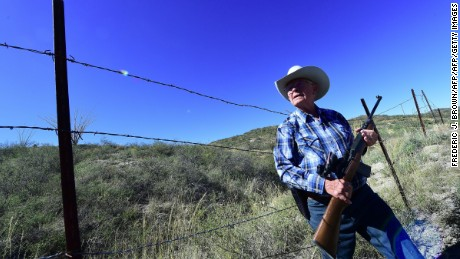 Cattle rancher Jim Chilton stands beside a fence that is the US-Mexico border on part of his 50,000 acre ranch on October 14, 2016 some 20 miles southeast of Arivaca, Arizona, where a barbed-wire fence is all that separates the two countries. Despite the difficult Sonoran desert terrain, the area remains a popular and much-used route by the drug mules, sophisticated and well-equipped with binoculars and satphones to monitor routes and US border patrols from the surrounding hilltops.   / AFP / Frederic J. BROWN        (Photo credit should read FREDERIC J. BROWN/AFP/Getty Images)