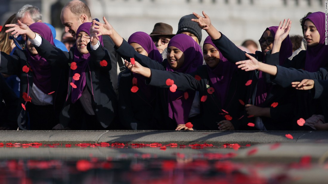 Young students in London scatter poppies into a fountain at Trafalgar Square after observing a two-minute silence in honor of Armistice Day. In advance of Armistice Day, many people in Britain wear a paper red poppy to symbolize the poppies that grew on French and Belgian battlefields during World War I.