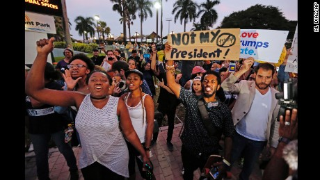 Protesters march Friday at Bayfront Park in Miami.