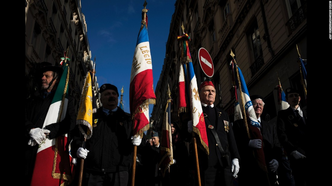 French veterans hold flags Friday, in a street of Lyon, France during the Armistice Day ceremony marking the 98th anniversary of the end of World War I.