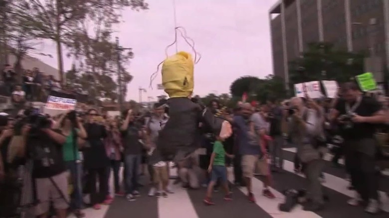 Children take a swing at anti-Trump protest piñata