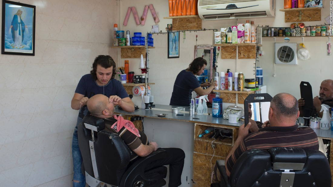 Life goes on at Ashti camp, which has restaurants, coffee shops and stores. Here, a man gets a shave and a haircut at the local barber.