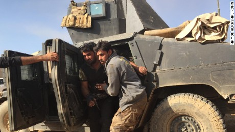 A wounded soldier is pulled out of his armored Humvee after returning from the front line.