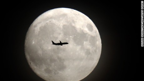 A commerical jet flies in front of the moon on its approach to Heathrow airport