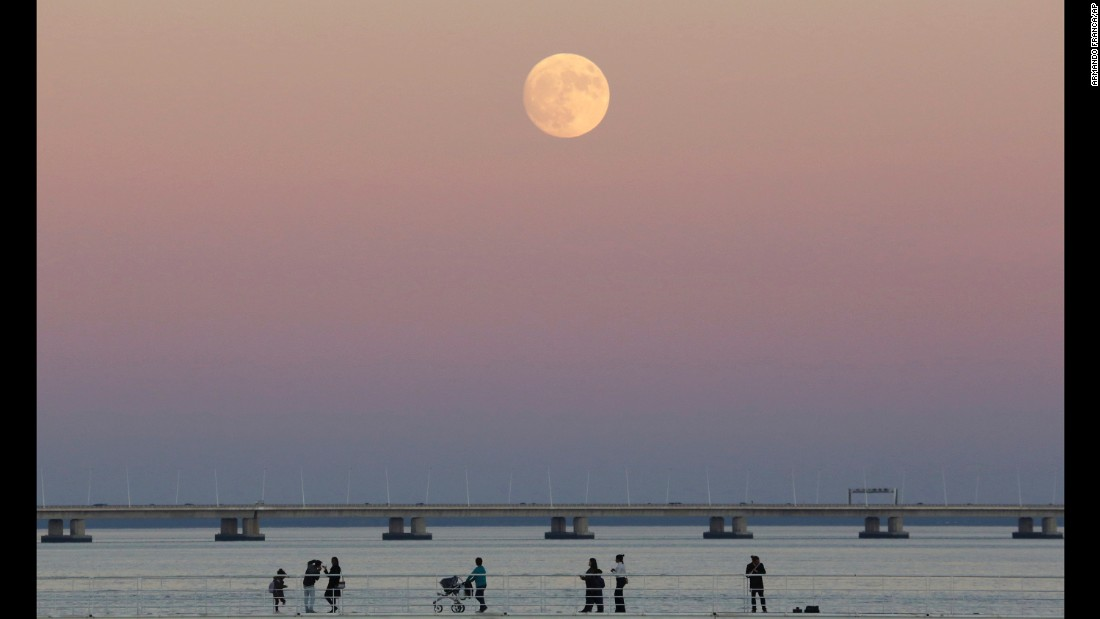 People stroll along the Tagus riverside as the moon rises in Lisbon, Portugal, on November 13.