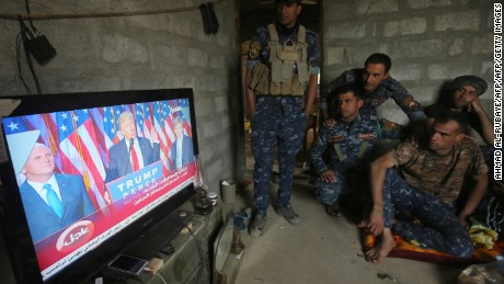 Members of the Iraqi forces watch Donuld Trump giving a speech after he won the US president elections in the village of Arbid on the southern outskirts of Mosul on November 9, 2016