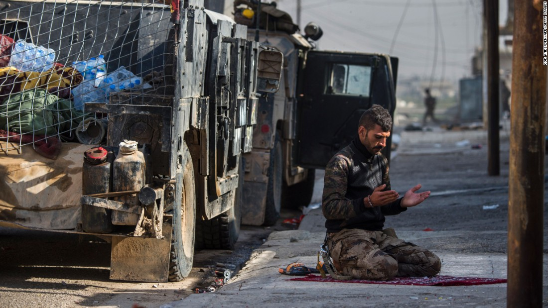 An Iraqi special forces soldier prays next to a Humvee before troops pushed toward Mosul's Karkukli neighborhood on November 13.