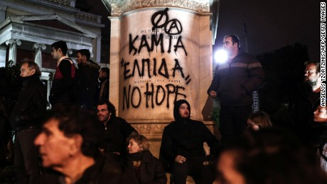 "Protesters stand in front of graffiti that reads ""No Hope"" on Tuesday in Athens."