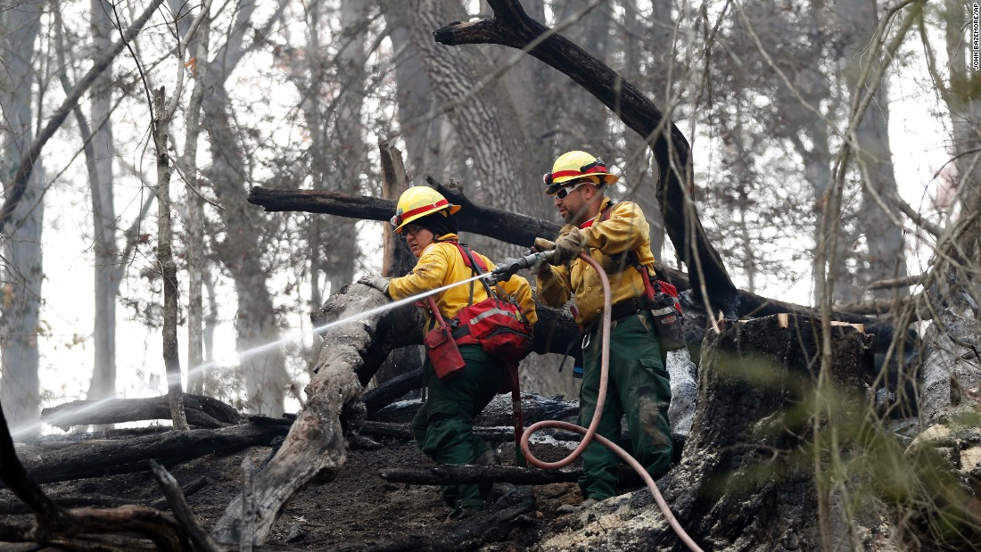 Firefighters Valarie Lopez and Mark Tabaez work to cool hot spots in Clayton on November 15. A number of the fires are being investigated as suspected arson, but weather conditions are also responsible for the fires.