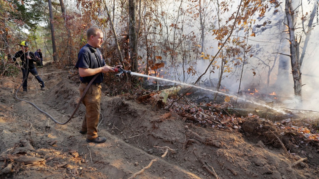 Assistant Fire Chief Brent Masey sprays water on a wildfire in Soddy-Daisy, Tennessee, on Thursday, November 10.