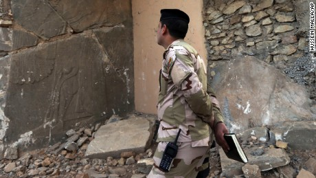An Iraqi army officer looks at a damaged carved stone slab, destroyed by ISIS militants, in Nimrud.
