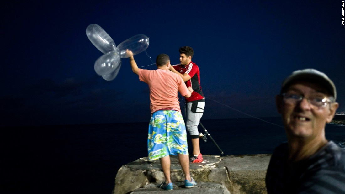People use inflated condoms to help them catch fish in Havana, Cuba, on Saturday, November 12. The condoms keep the bait high in the water and increase the line's resistance against the pull of heavy fish.