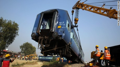Rescuers lift one of the 14 coaches of an overnight passenger train that rolled off the track near Pukhrayan village Kanpur Dehat district, Uttar Pradesh state, India, Sunday, Nov. 20, 2016.