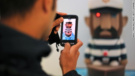 A visitor uses his mobile phone to photograph a work of art entitled 'Captain Fairtrade' made from sugar coated sponge, during a exhibition of edible art in London, on August 27, 2010.   AFP PHOTO / BEN STANSALL (Photo credit should read BEN STANSALL/AFP/Getty Images)