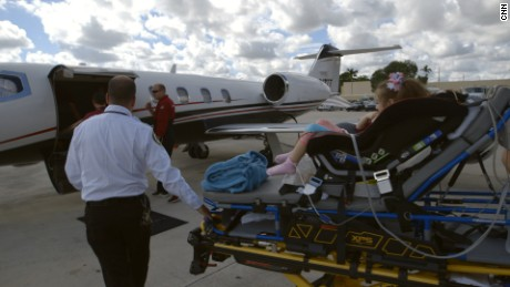 Paramedics transport Abby Muszynski to the air ambulance that will fly her from Florida to Colorado.