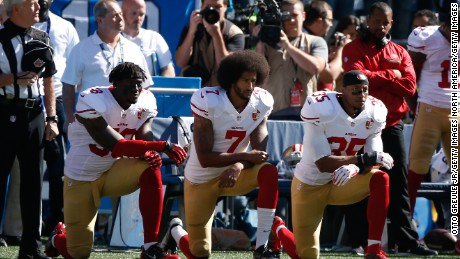Colin Kaepernick, center, and two teammates kneel for the national anthem at a September 2016 game.