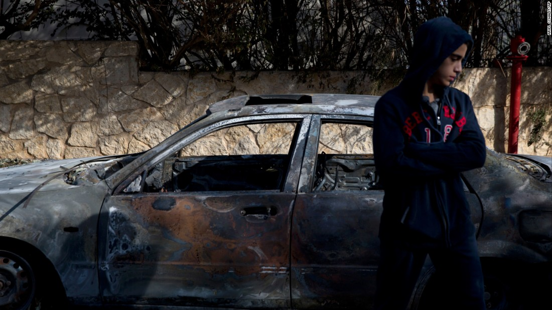 A boy stands next to a burnt car in Zikhron Ya'akov on November 23.