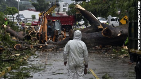 Workers cut a tree that killed a boy when it fell during a storm in Panama City on November 22, 2016. Tropical Storm Otto, that is expected to become a full-on hurricane in the Caribbean, was lurching toward Central America on Tuesday, with its rainy fringe already causing three deaths in Panama and prompting coastal evacuations in Costa Rica. In Panama, three people died from a mudslide and a falling tree provoked by the first outer dump of Otto's heavy rains, the head of the National Civil Protection Service, Jose Donderis, told AFP.  / AFP / Rodrigo ARANGUA        (Photo credit should read RODRIGO ARANGUA/AFP/Getty Images)