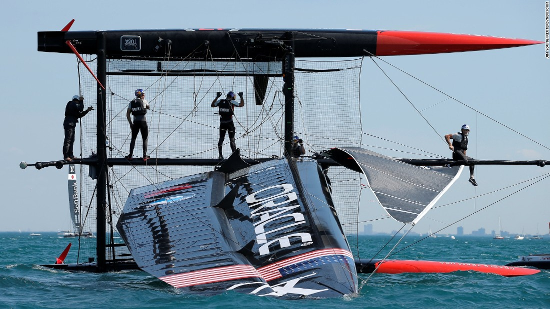The crew of Oracle Team USA stands on its capsized boat during a practice session in Chicago on Friday, June 10.