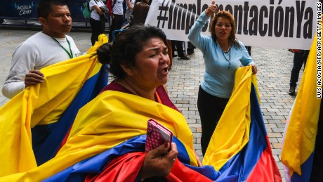 People shout slogans during a demo for the immediate implementation of the agreement between the Colombian government and the FARC guerrillas at Bolivar Square in Bogota on November 18, 2016. / AFP / Luis Acosta        (Photo credit should read LUIS ACOSTA/AFP/Getty Images)