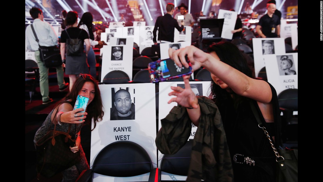 People take selfies where celebrities would be sitting at the MTV Video Music Awards in August.