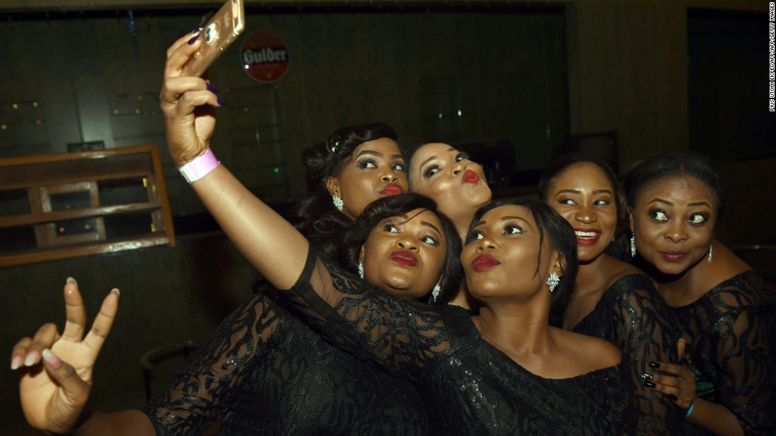 The spectacular growth in mobile demand should result in 730 million individual subscribers by 2020. It's market is second only to that of the Asia-Pacific region.<br /><br />Pictured: Hostesses take a selfie during the African Footballer of the Year Award in Abuja, Nigeria on January 7, 2016.