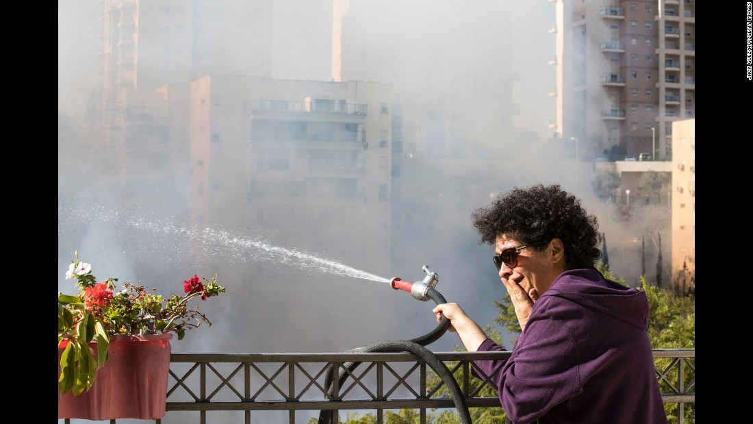 A woman sprays water toward a fire from a rooftop in Haifa on November 24.