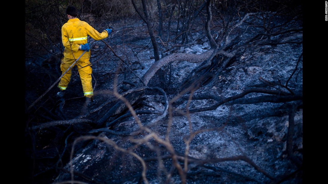 A firefighter extinguishes smoldering ashes in Zikhron Ya'akov, south of Haifa, on Wednesday, November 23.